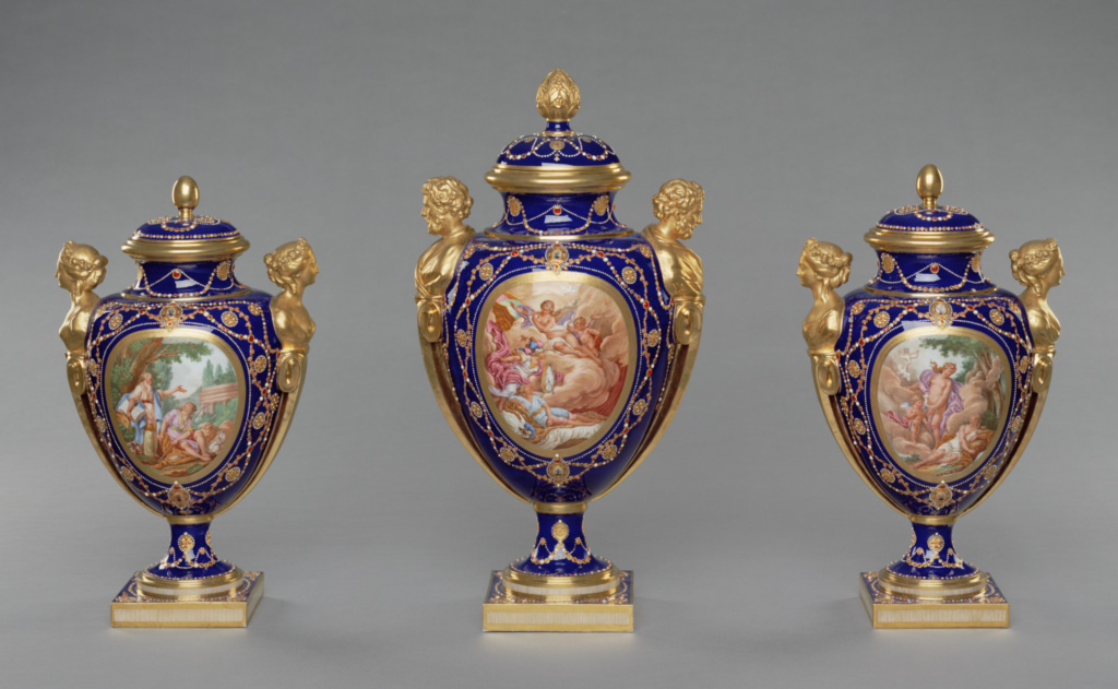 Garniture of Three Vases (vases des âges); Shape designed by Jacques-François Deparis (French, active 1746 - 1797), at least one vase modelled by the répareur Etienne-Henry Bono (French, active 1754 - 1781), reserves painted by Antoine Caton (French, active 1753 - 1798), Gilded by Etienne-Henri Le Guay (French, 1719/1720 - about 1799), Enamel jeweling by Philippe Parpette (French, active 1755 - 1757, 1773 - 1806), after engravings by Jean-Baptiste Tilliard (French, 1686 - 1766), after designs by Charles Monnet (French, 1732 - after 1808), Sèvres Manufactory (French, founded 1756); 1781; Soft-paste porcelain, beau bleu ground color, polychrome enamel decoration, enamel imitating jewels, gilding, and gold foil; 84.DE.718; The J. Paul Getty Museum, Los Angeles; Rights Statement: No Copyright - United States