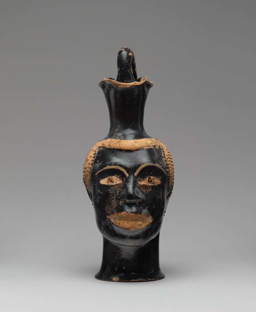 Pitcher (Oinochoe) in the Form of a Black African Male Head; Attributed to Class B bis: Class of Louvre H 62 (Greek (Attic)); Athens, Greece; about 510 B.C.; Terracotta; 21.5 × 8.9 × 12.7 cm (8 7/16 × 3 1/2 × 5 in.); 83.AE.229; The J. Paul Getty Museum, Villa Collection, Malibu, California; Rights Statement: No Copyright - United States
