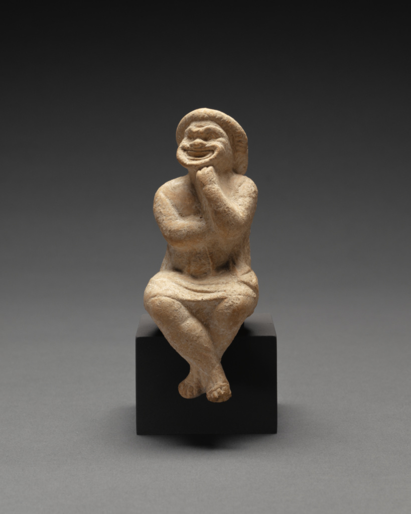 Statuette of a Seated Comic Actor; Unknown; Apulia, South Italy; 400–200 B.C.; Terracotta with white slip; 10.3 × 4.1 × 6.4 cm (4 1/16 × 1 5/8 × 2 1/2 in.); 96.AD.164; The J. Paul Getty Museum, Villa Collection, Malibu, California, Gift of Barbara and Lawrence Fleischman; Rights Statement: No Copyright - United States