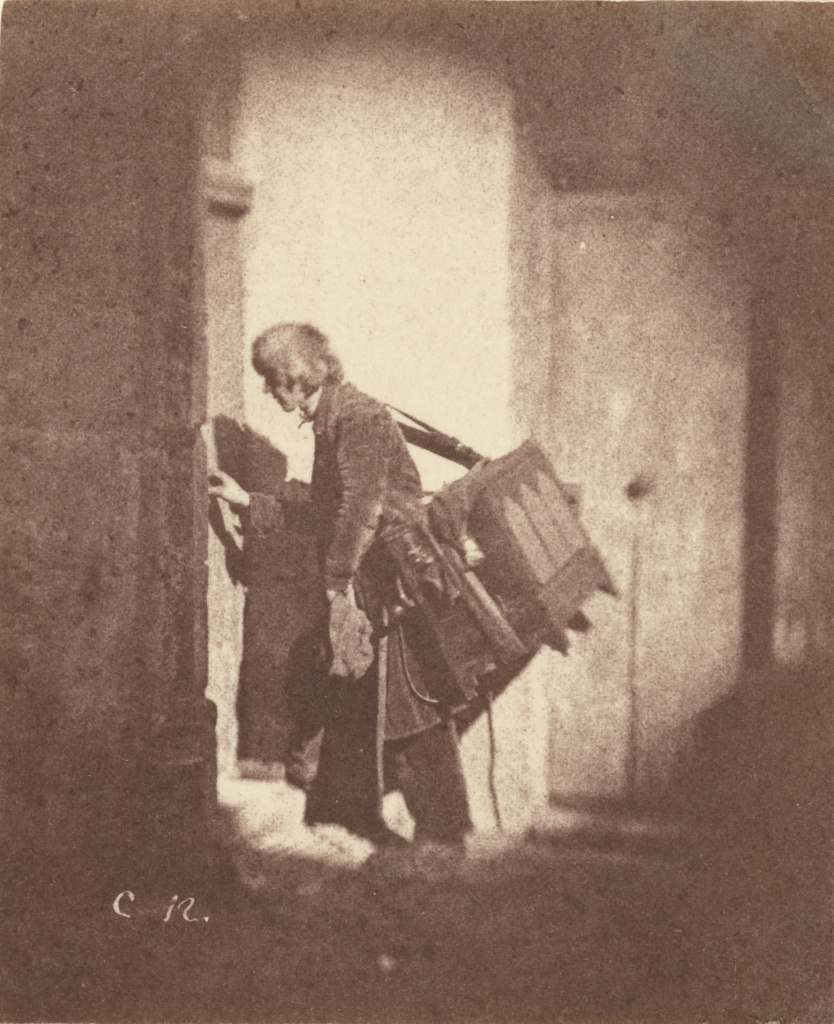 [Organ Grinder at 21, quai Bourbon, Ile Saint-Louis, Paris]; Charles Nègre (French, 1820 - 1880); Paris, France; before March or May 1853; Salted paper print from a paper negative; 10 × 8.3 cm (3 15/16 × 3 1/4 in.); 84.XM.344.1; The J. Paul Getty Museum, Los Angeles; Rights Statement: No Copyright - United States