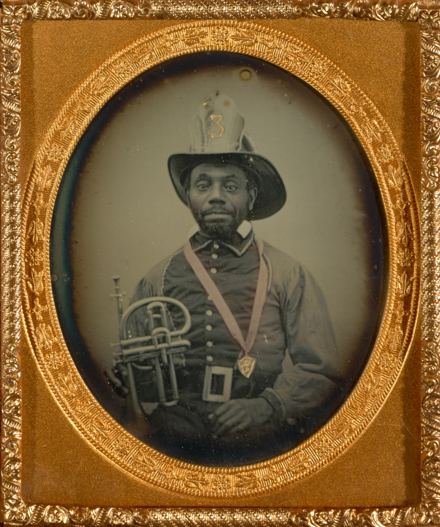 [Fireman in Uniform Holding a Brass Musical Instrument]; Unknown maker, American; 1855–1856; Hand-colored daguerreotype; 6 × 4.9 cm (2 3/8 × 1 15/16 in.); 84.XT.1582.3; The J. Paul Getty Museum, Los Angeles; Rights Statement: No Copyright - United States