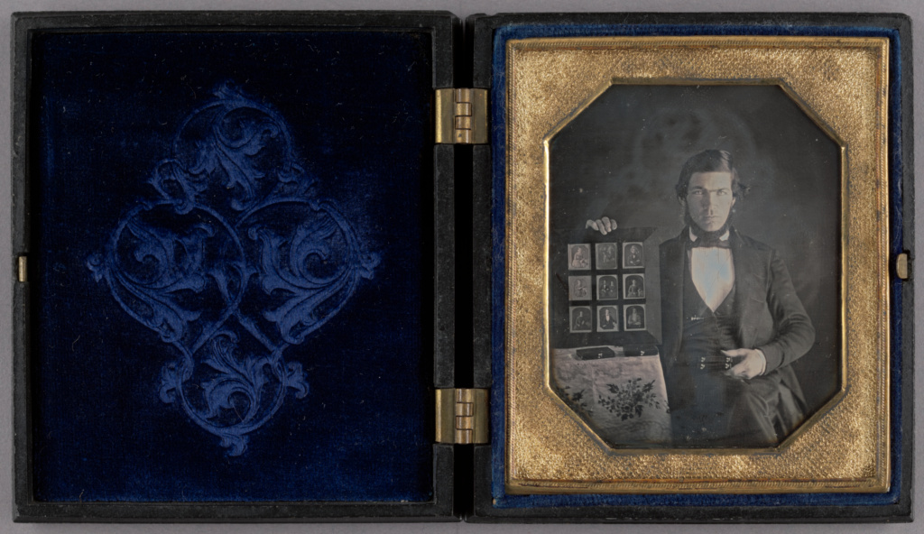 Portrait of a Daguerreotypist Displaying Daguerreotypes and Cases; Unknown maker, American; 1845; Daguerreotype, hand-colored; 84.XT.1576.1; Rights Statement: No Copyright - United States