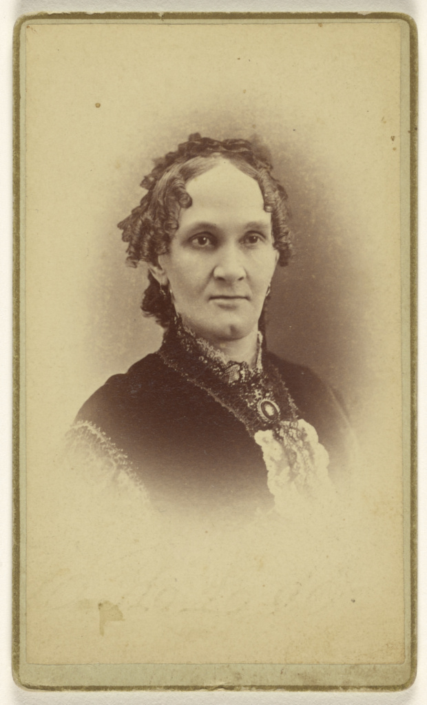 [Unidentified woman with short curly hair, wearing a cameo, printed in vignette-style]; Beer & Company; 1870–1875; Albumen silver print; 84.XD.1157.1048; The J. Paul Getty Museum, Los Angeles; Rights Statement: No Copyright - United States