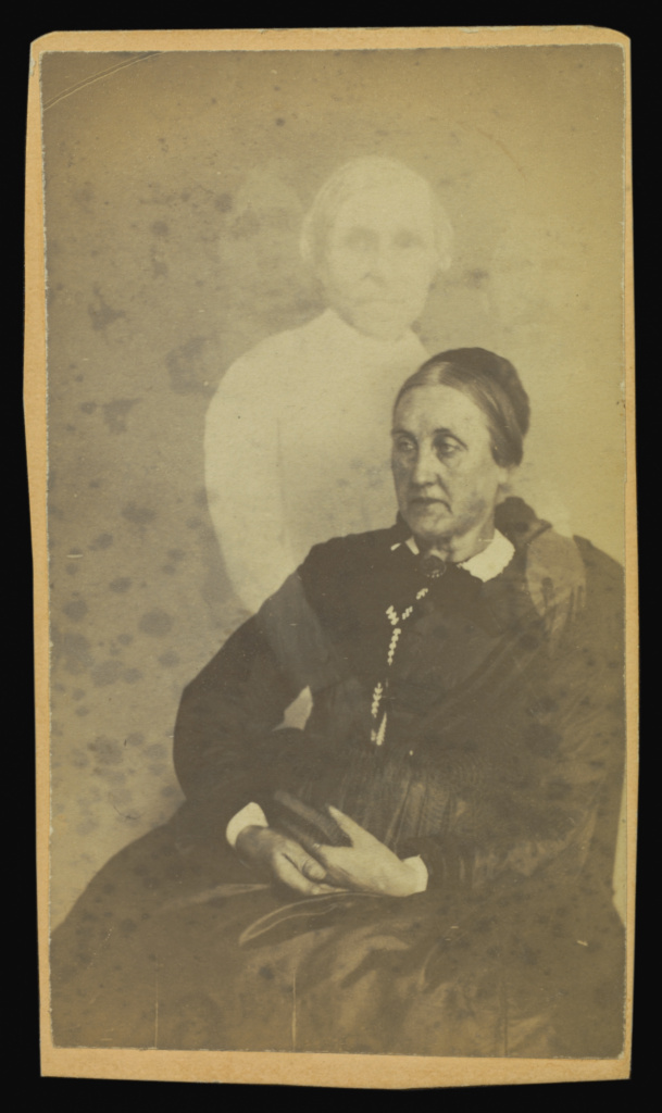 """[Unidentified elderly woman seated, three """"spirits"""" in the background]; William H. Mumler (American, 1832 - 1884); Boston, Massachusetts, United States; 1862–1875; Albumen silver print; 9.9 × 5.8 cm (3 7/8 × 2 5/16 in.); 84.XD.760.1.19; The J. Paul Getty Museum, Los Angeles; Rights Statement: No Copyright - United States"""
